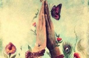 Manos juntas con mariposa para representar el significado de la palabra namasté