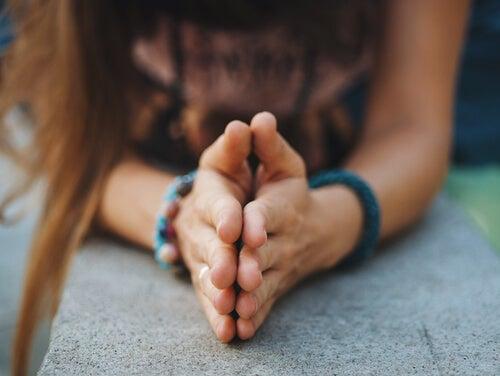 Mujer juntando sus manos sobre una piedra
