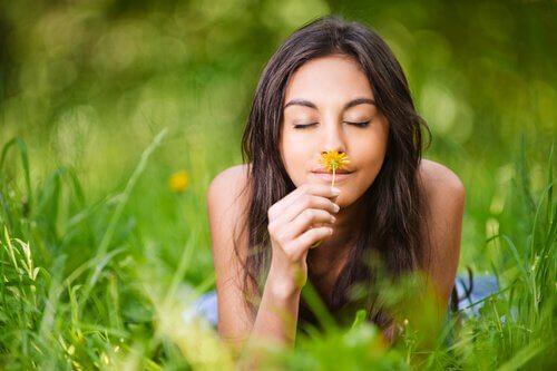 Mujer con una sonrisa oliendo una flor