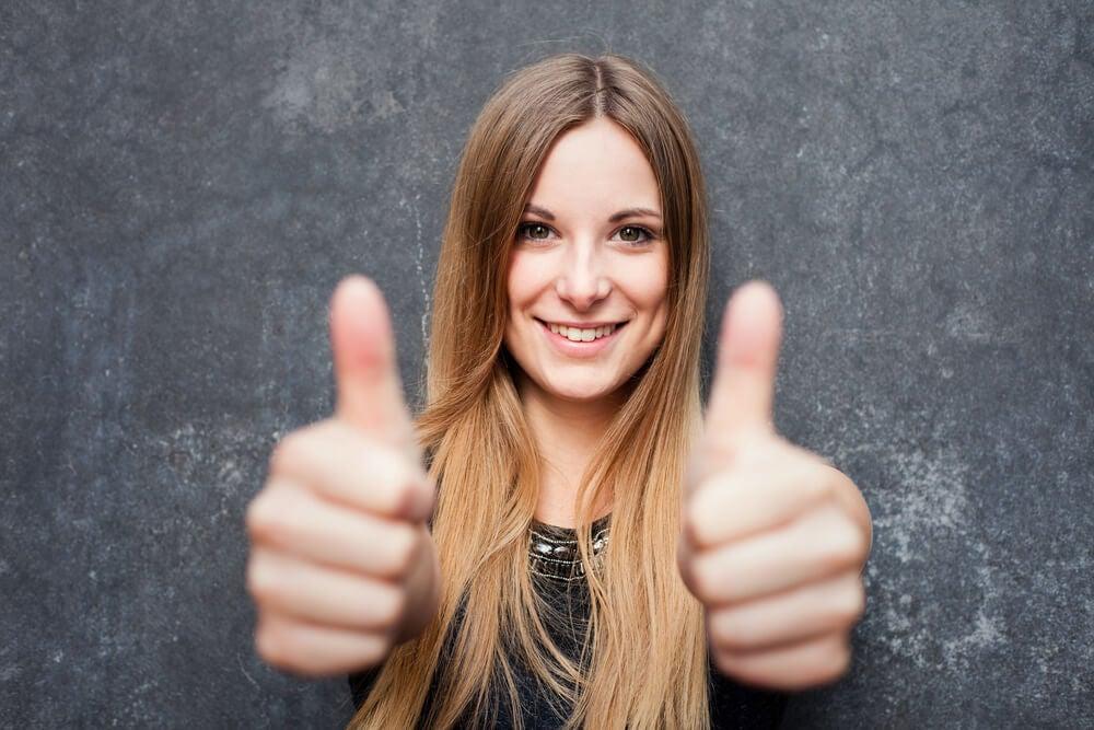Mujer con actitud positiva alzando el pulgar