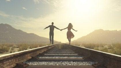 Pareja agarrada de la mano por la vía del tren para representar la idealización