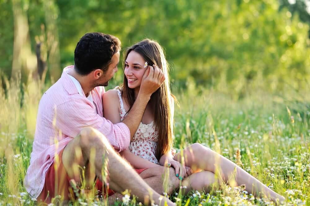 Casal apaixonado sentado na grama