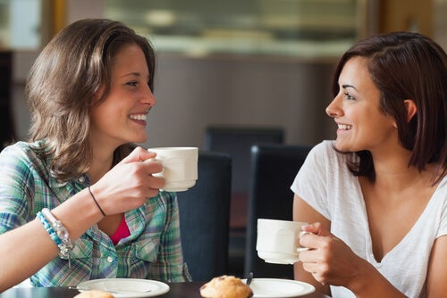 Amigas sonriendo mientras toman un café