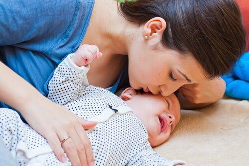 Madre acariciando y besando a su bebé