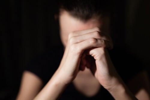 Mujer con manos entrelazadas pidiendo perdón