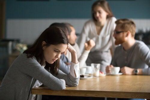 Mujer alejada de sus compañeros pensando que están en su contra
