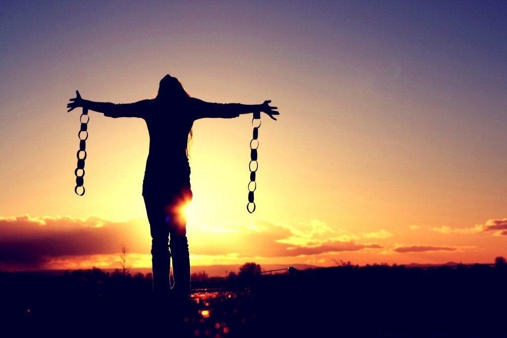 Mujer con cadenas rotas que se ha liberado de sus propias reglas