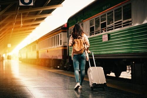 Mujer con una maleta en la estación del tren