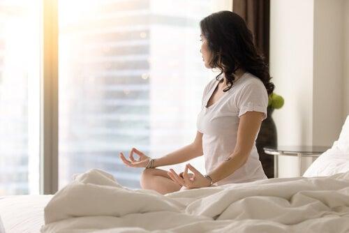 Mujer haciendo mindfulness en su habitación