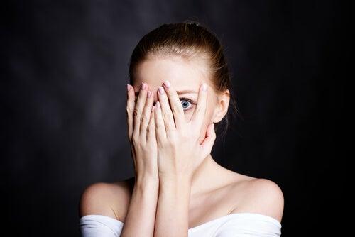 Mujer ocultando sus emociones al tapar su cara
