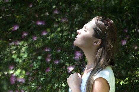 Mujer recordando mientras huele flores