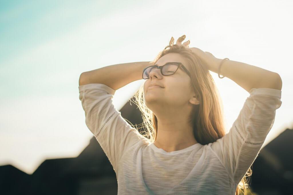 Mujer con los ojos cerrados practicando el optimismo