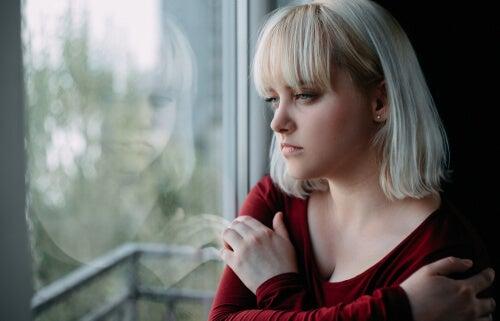 Mujer rubia mirando por la ventana pensando en los proyectos personales que se ha llevado la pandemia