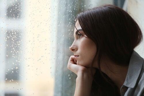 Mujer triste mirando la lluvia por la ventana