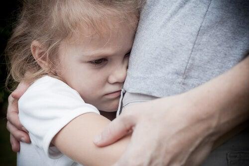 Niña con depresión abrazada a su mamá