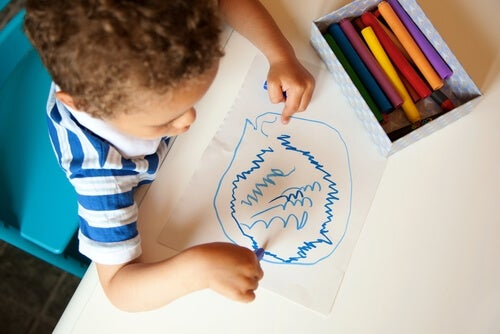 Niño dibujando garabatos en papel