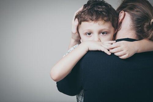 Niño traumatizado abrazando a su madre