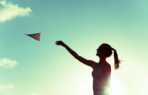 Mujer jugando con un avión de papel