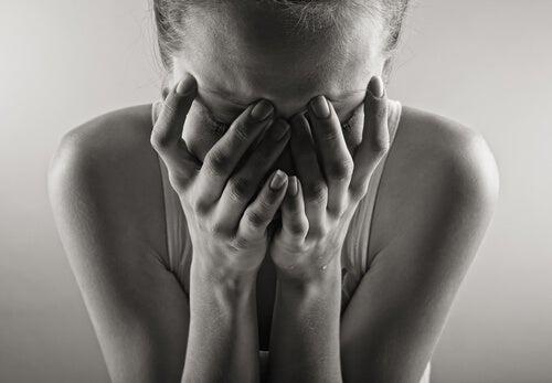 Mujer llorando con el rostro tapado