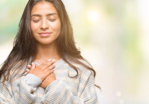 Mujer tranquila con las manos en el pecho