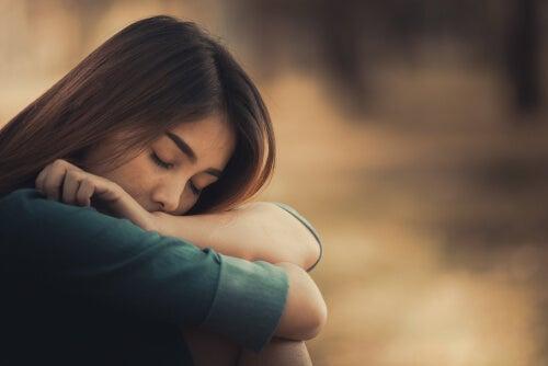 Mujer con tristeza recostada en sus brazos