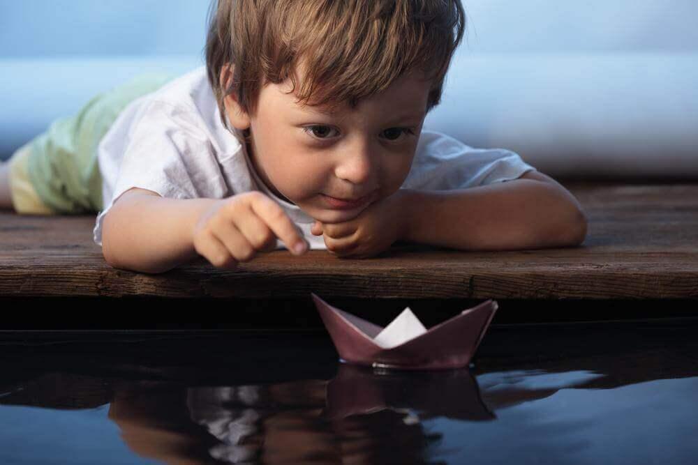 Niño jugando con barco de papel representando los beneficios de pensar en voz alta