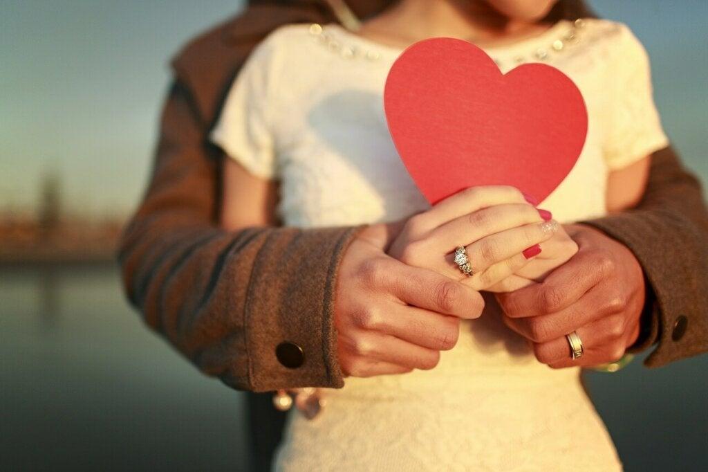 Personas abrazadas con corazón intentando lograr que el amor funcione según Robert J. Sternberg