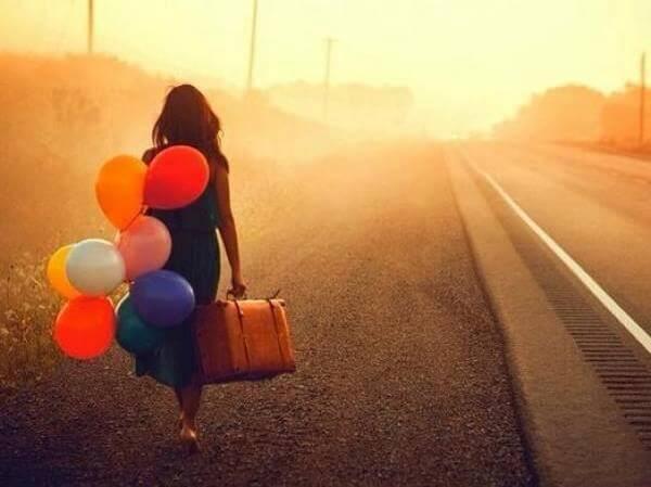 Mujer caminando con una maleta y globos de colores