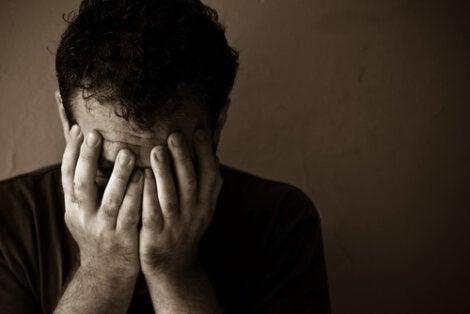 Hombre deprimido con las manos en el rostro