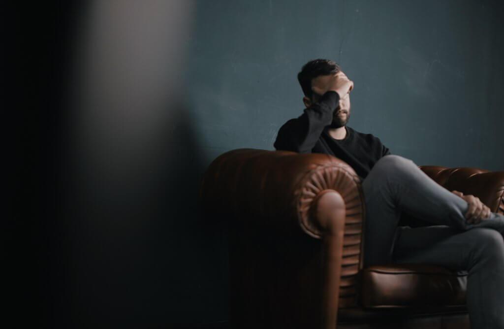 Hombre recordando en un sillón