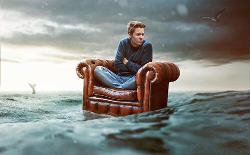 Hombre sobre un sofá en el mar rodeado de recuerdos