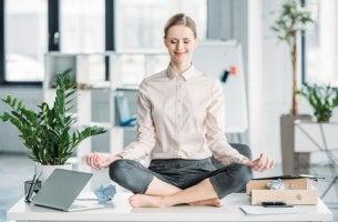 Mujer que sabe vivir el presente meditando en la oficina