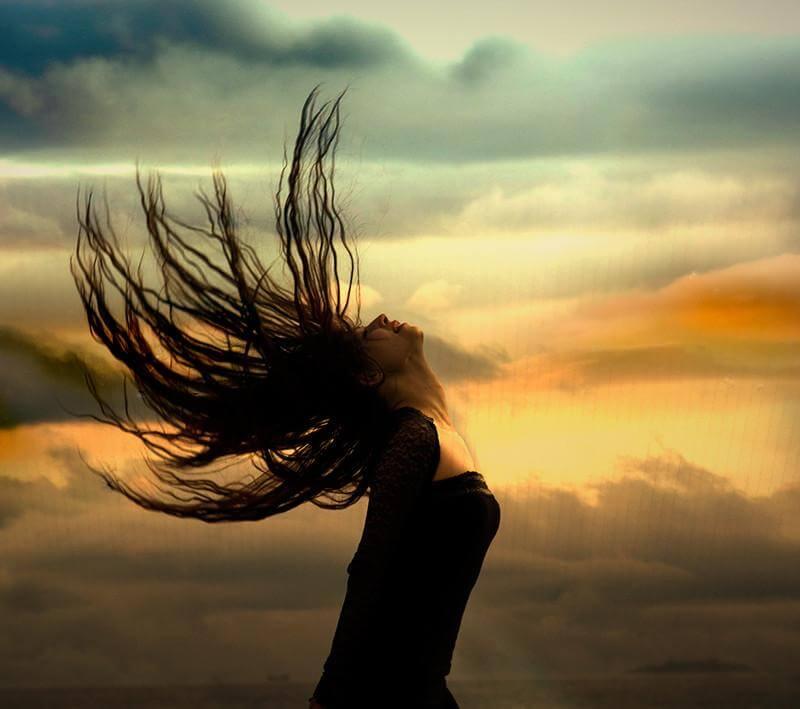 chica-mirando-hacia-arriba-con-cabello-al-viento