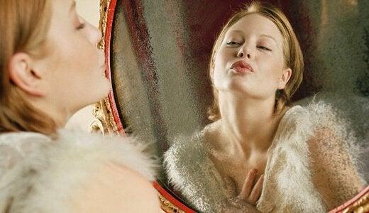 Chica mirándose a un espejo para aumentar la autoestima