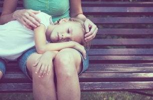 Hija triste con la cabeza apoyada en las piernas de su madre