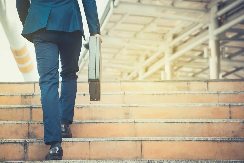 Hombre con portafolio subiendo escaleras
