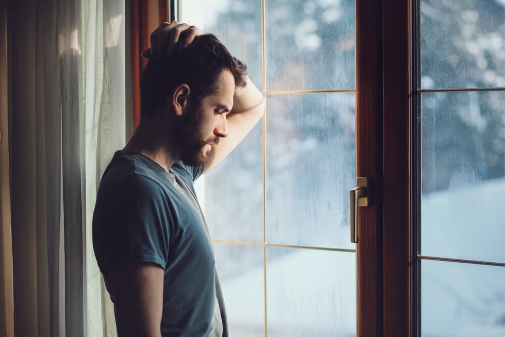 Hombre triste cerca de la ventana que toma Sertralina
