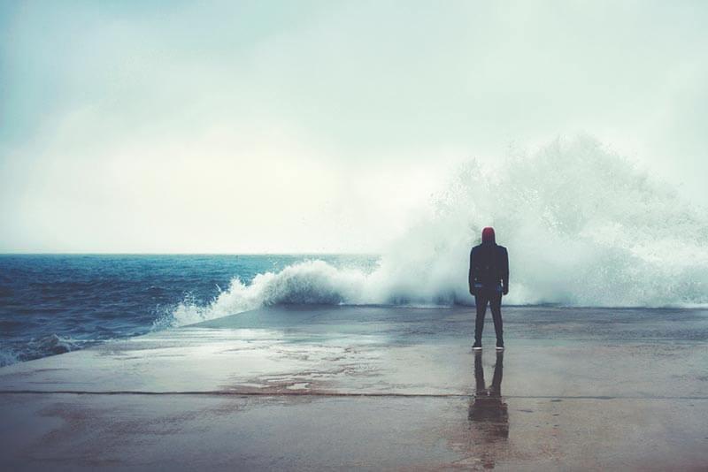 Hombre enfrente de un mar bravo