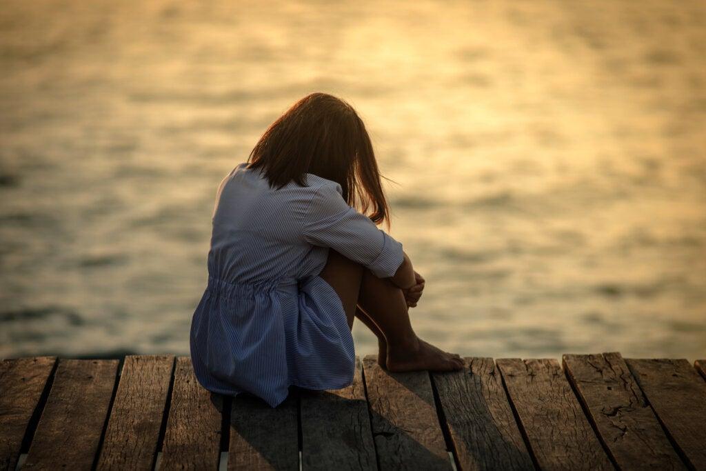 mujer sentada frente mar
