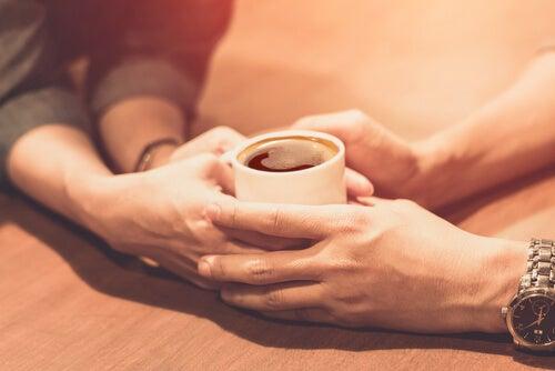 Pareja tomándose café agarrándose las mano