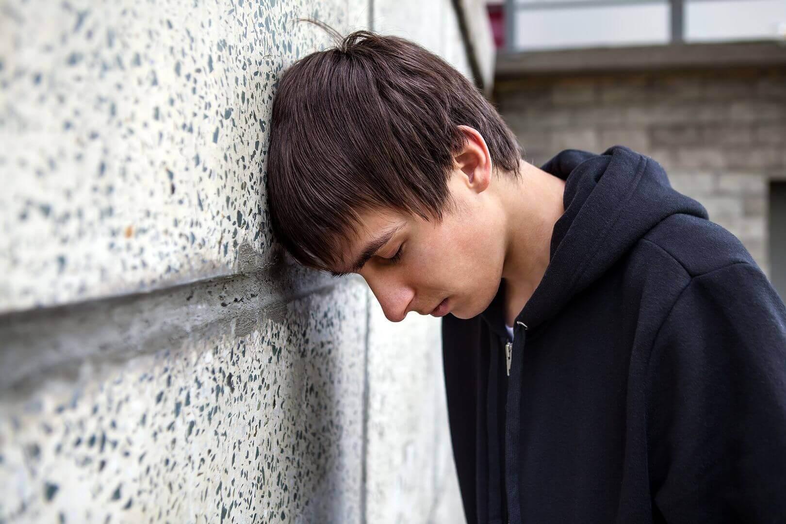 chico triste apoyando cabeza pared