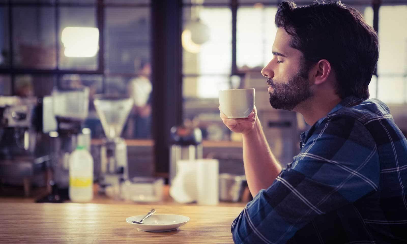 hombre oliendo taza cafe
