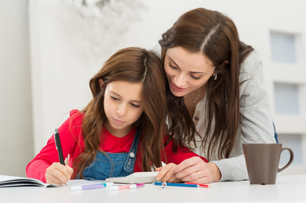 Madre ayudando a su hija con los deberes