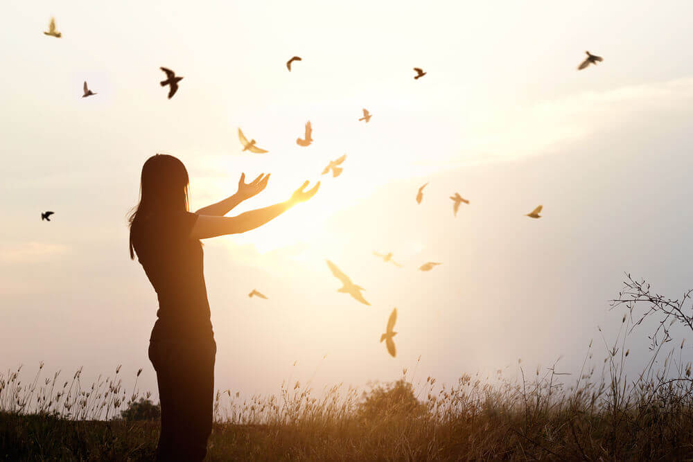 Mujer con pájaros volando