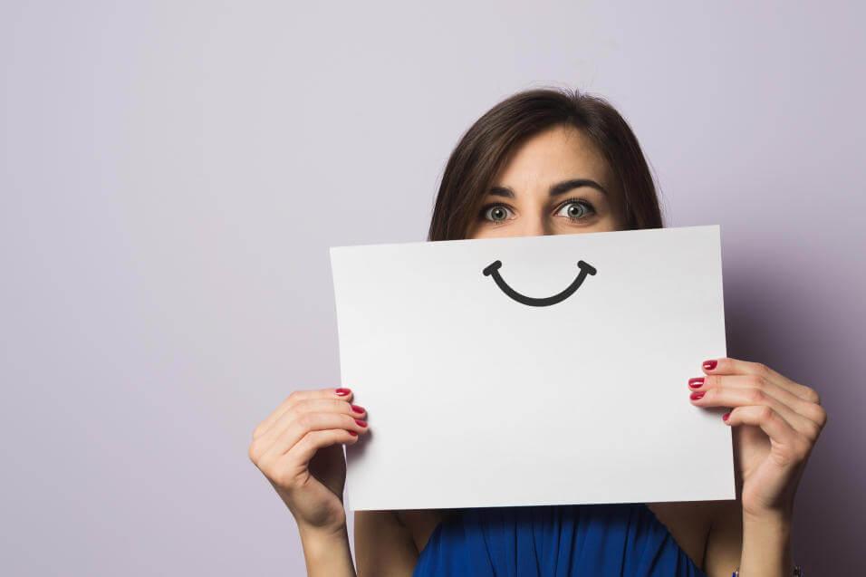 Mujer con sonrisa pintada en un papel