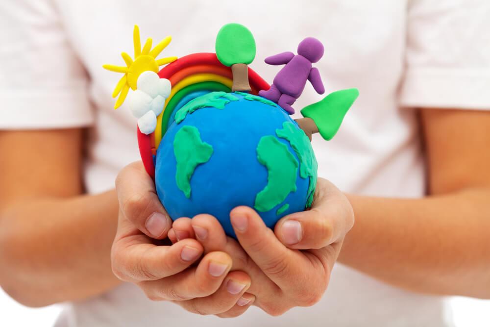 Niño con mundo hecho de plastilina entre las manos