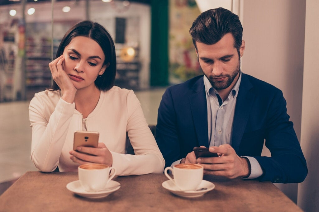 pareja mirando moviles sin hablar