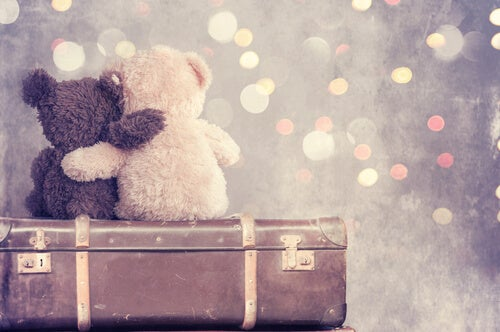 Osos de peluches abrazados encima de una maleta