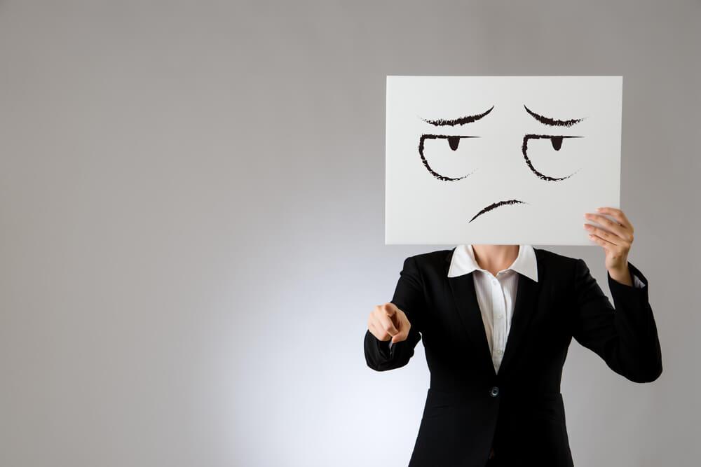 Mujer con un cartel con una cara triste en la cara