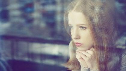 chica mirando por ventana y pensando en la disonancia cognitiva